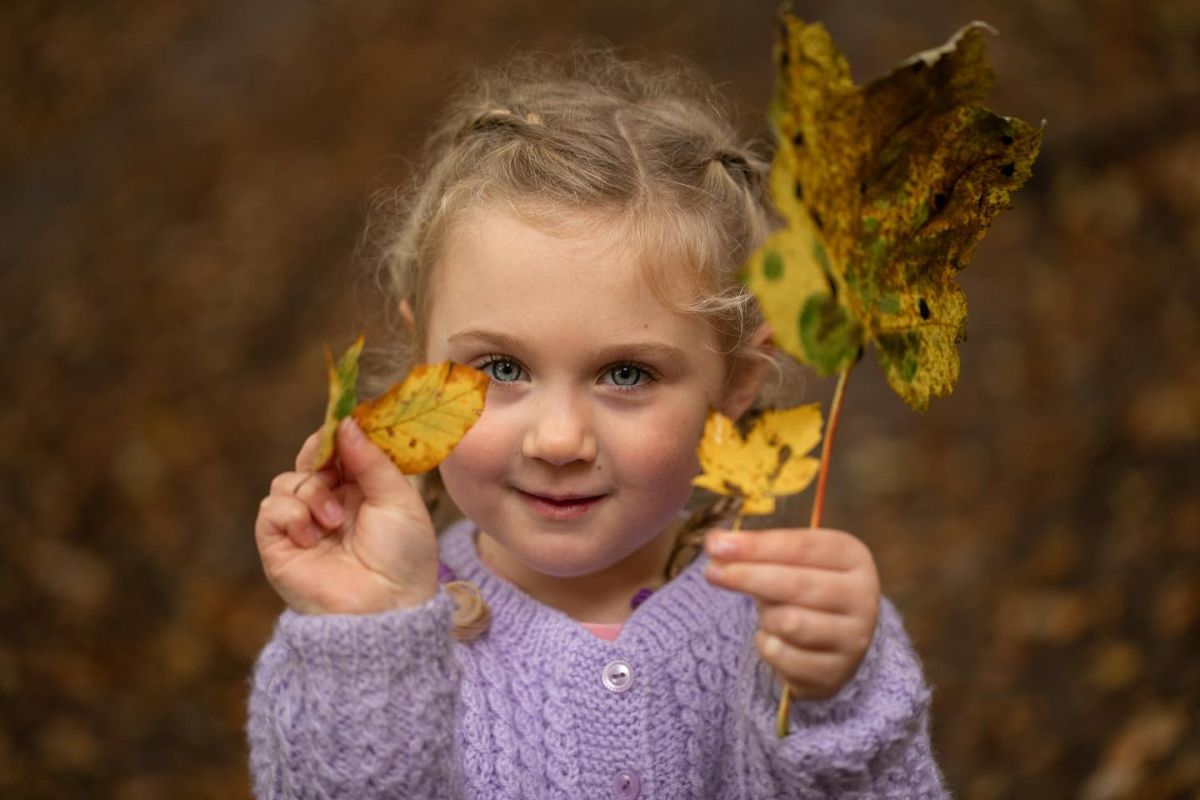 Autumn photograph pf a young girl holding yellow leaves taken by Borders Photographer
