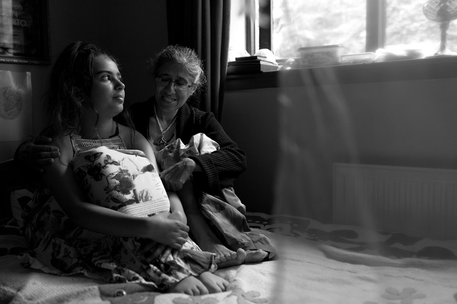 Mother and daughter cuddled in on the childs bed under the window