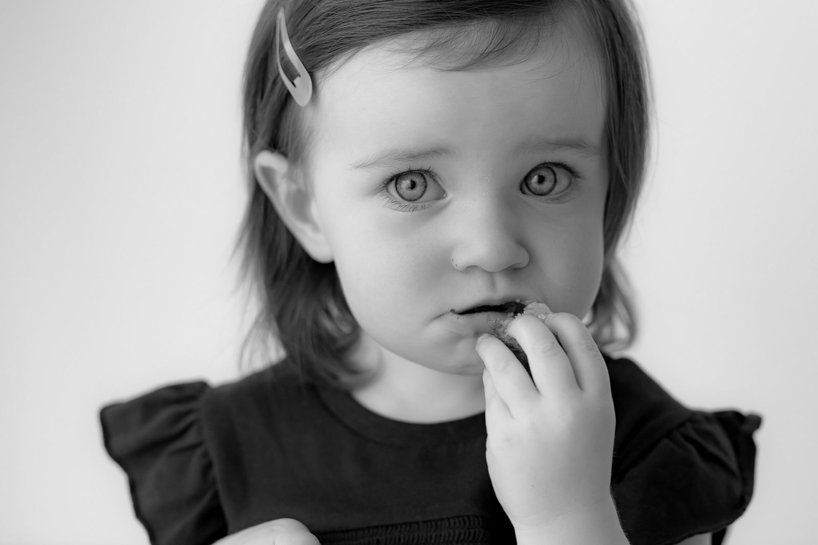 Beautiful girl with blue eyes snacking as the photographer is taking a close up head shot