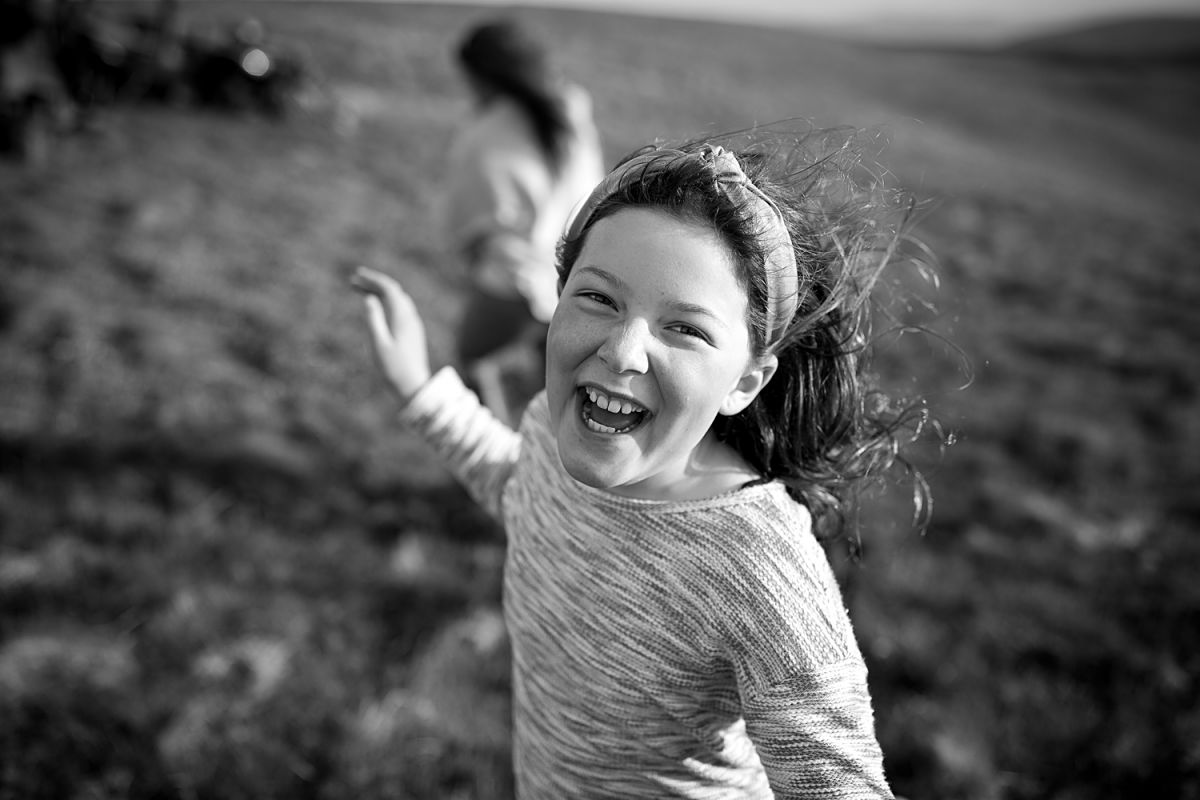 Peebles Photographer capturing happy giggling girl on her farm, with the wind blowing in her hair.
