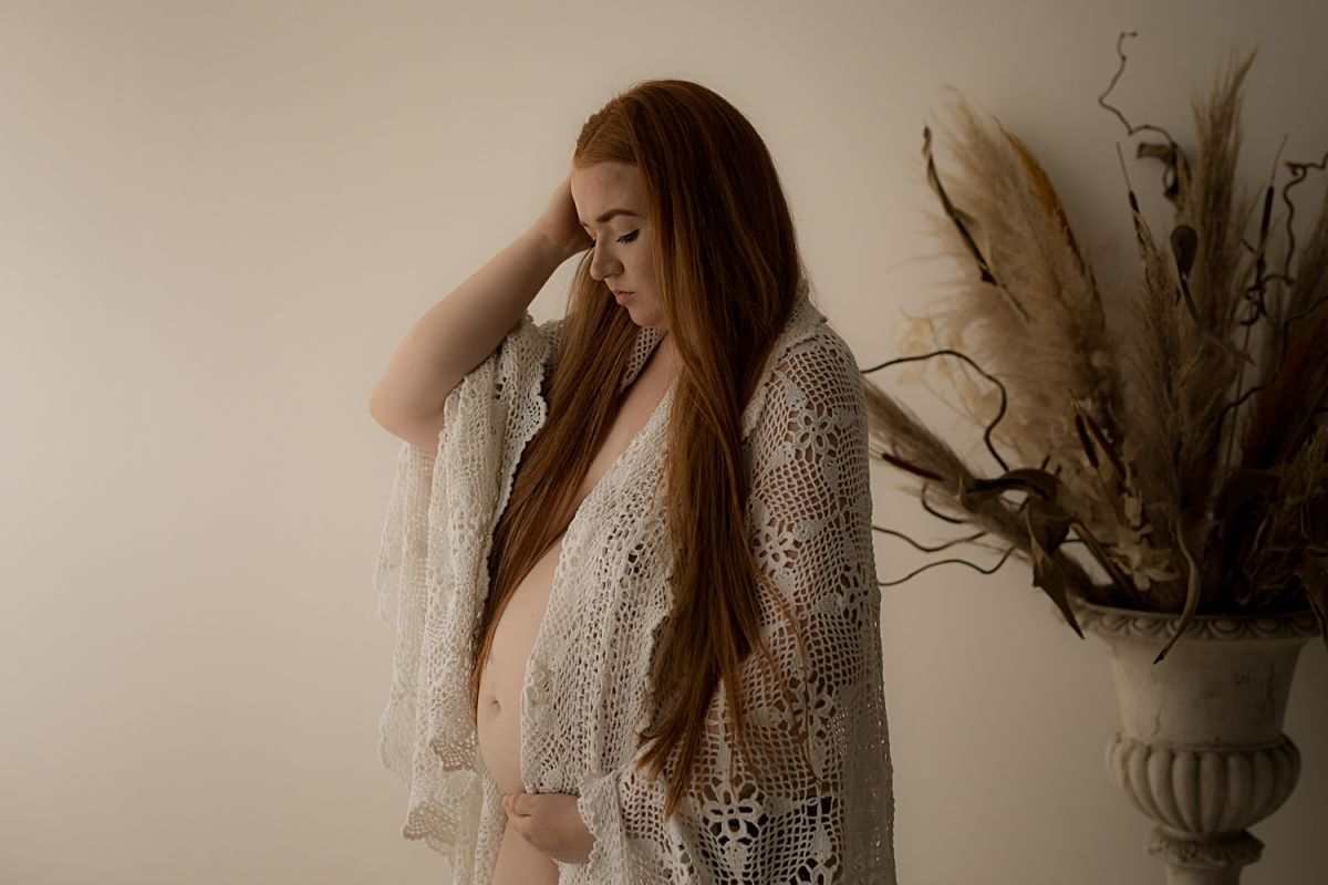 Pregnant mother in a shawl with her bump on show taken by Enamay Photographh